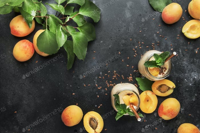 Healthy apricot smoothies in glass bottles and fresh fruits