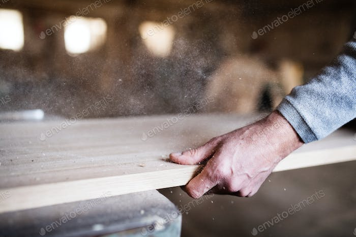 An unrecognizable man worker in the carpentry workshop, working with wood.