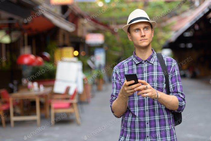 Porträt von jungen gutaussehenden Touristen Mann mit Telefon in den Straßen
