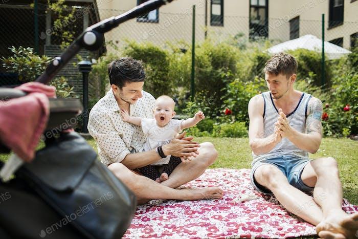 Fröhliches Baby Mädchen mit Homosexuell Männer applaudieren auf Hof