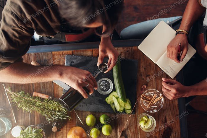 Two barmen creating new cocktail recipe