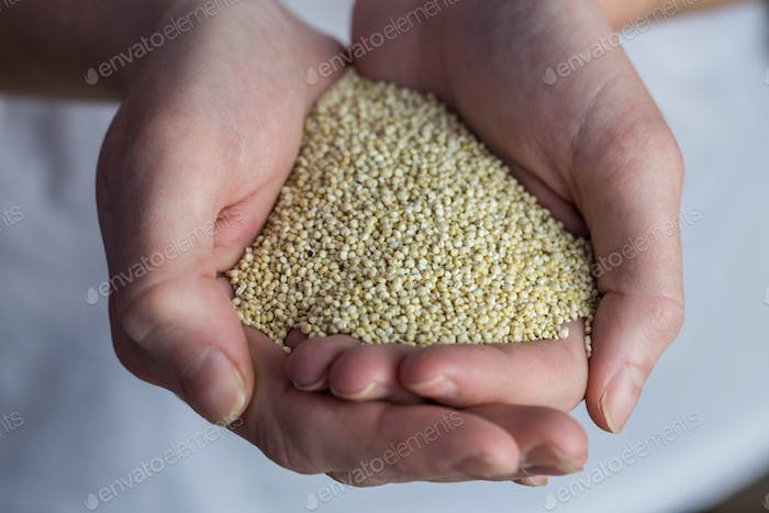 Woman showing handful of sesame seed in close up