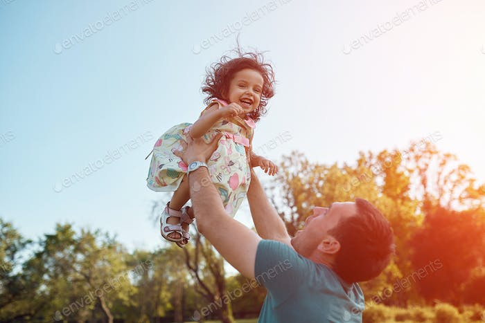 Happy father and daughter laughing together outdoors