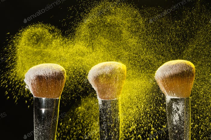 Mineral make up and objects concept - Three make up brushers in yellow dust over dark background