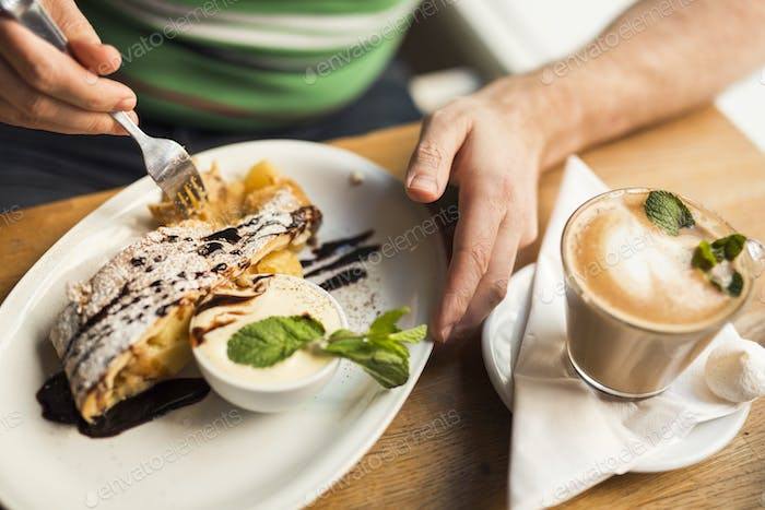 Sweden, Stockholm, Gamla Stan, Man having dessert and coffee in cafe, close up of hands