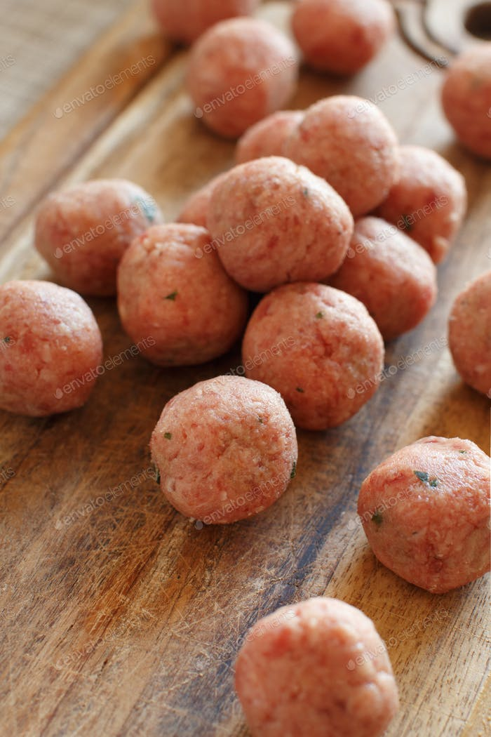 Raw meatballs ready to cook on a wooden board