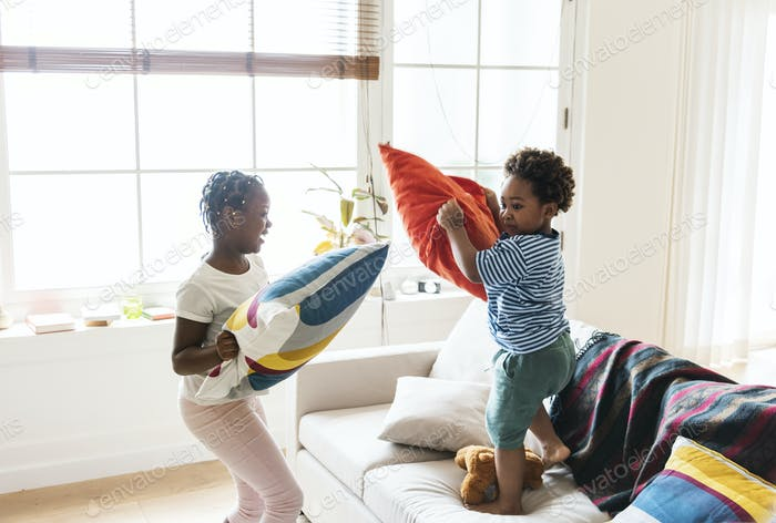 Brother and sister pillow fighting in living room