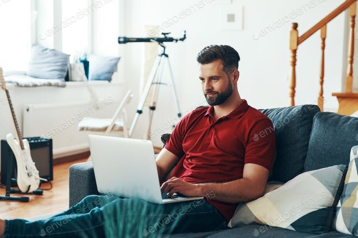 Handsome young man in casual clothing using laptop and smiling while sitting on the sofa