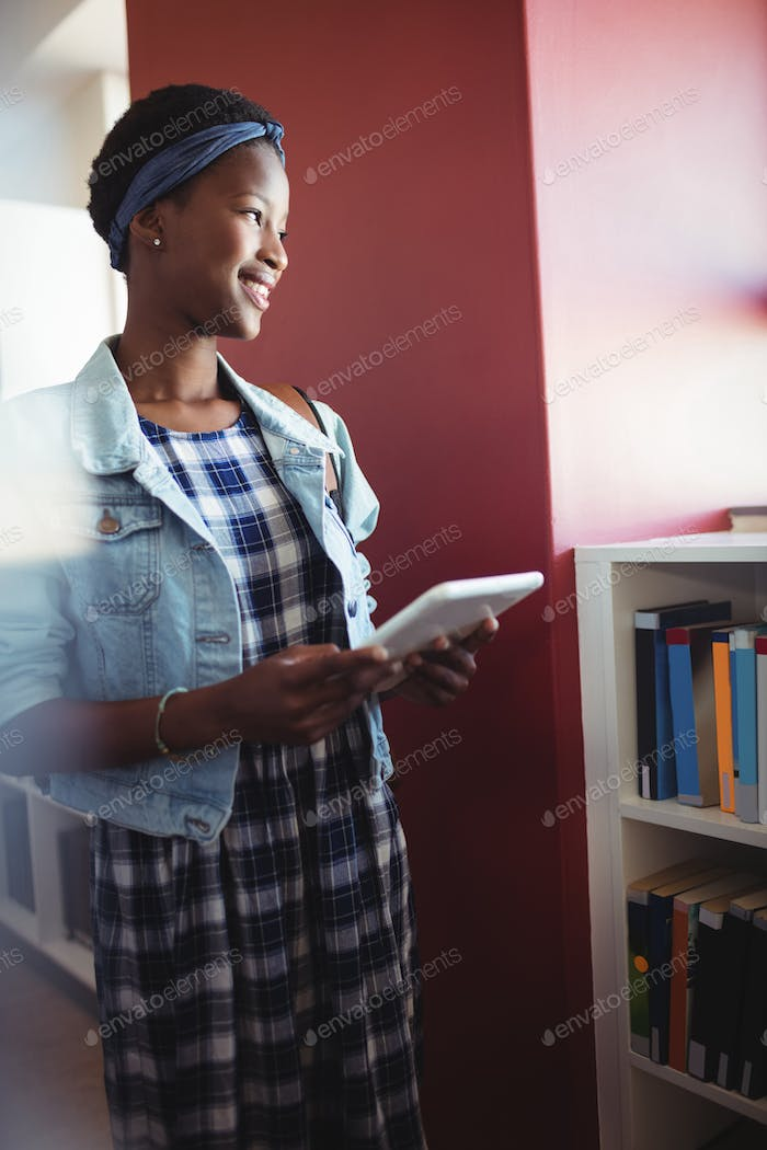 Smiling schoolgirl using digital tablet in library