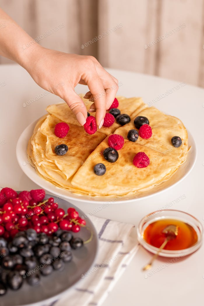 Hand of young female or housewife taking fresh raspberry from top of pancake