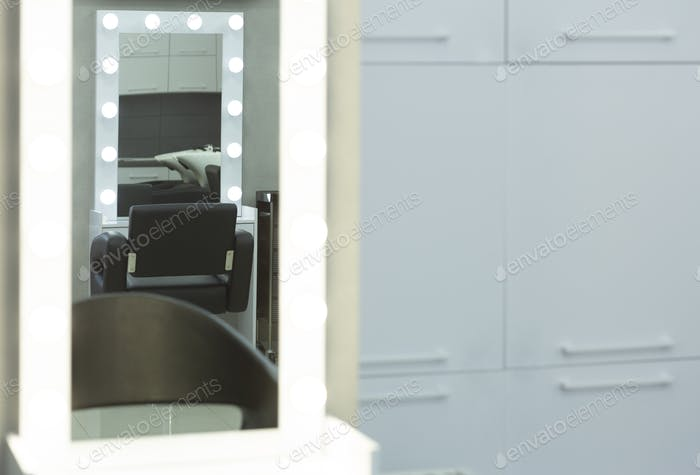 Mirror reflects barber chair and wash sink
