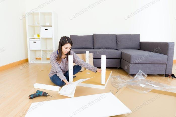 Woman assembling cupboard
