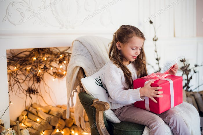 Happy child girl sitting on armchair covered with a blanket against decorated christmas fireplace