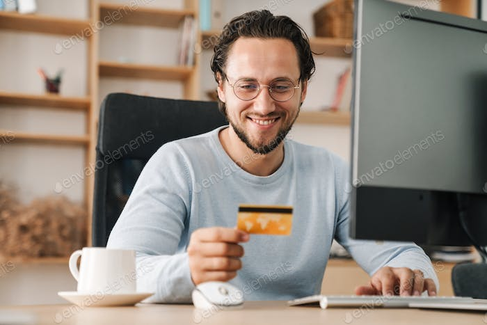 Image of programmer man holding credit card while working with computer