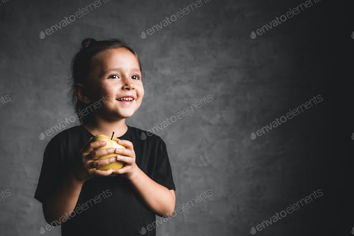 Portrait of a happiness little girl eating a green apple on gray background