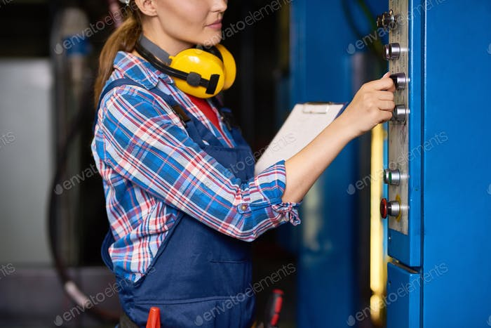 Female Technician Operating Machines at Factory