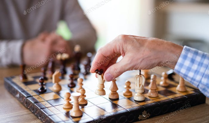 Midsection of senior men friends at home, playing chess