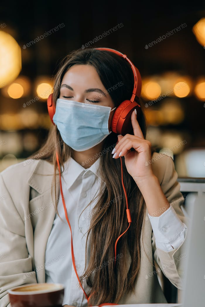 A girl sitting in a coffee shop with headphones. Coronavirus outbreak