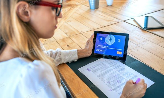 Mujer de negocios con tableta con ethereum información de trabajo