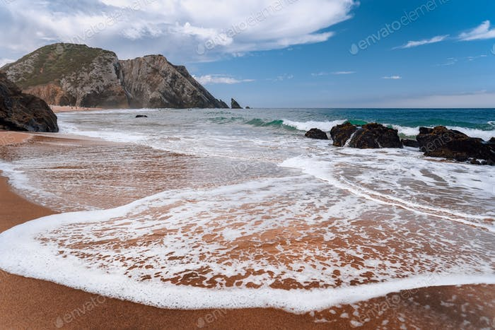 Praia da Adraga at atlantic ocean, Portugal. Foamy wave at sandy beach with picturesque landscape