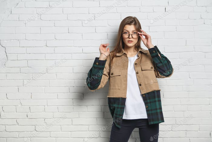 Portrait of young hipster woman in eyeglasses over white brick wall. Eyesight consept