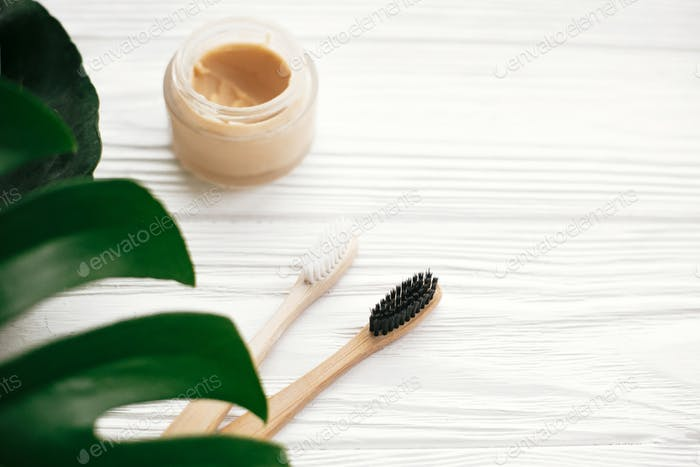 Natural eco friendly bamboo toothbrushes on white wood with green monstera