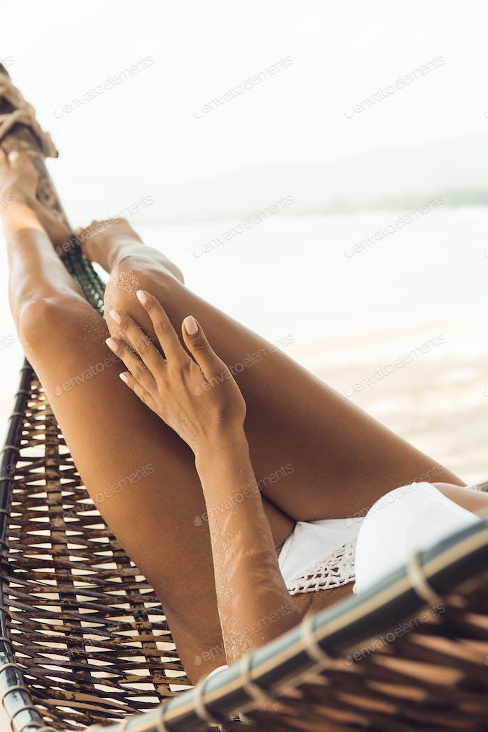 Sexy girl relax in hammock on tropic beach.
