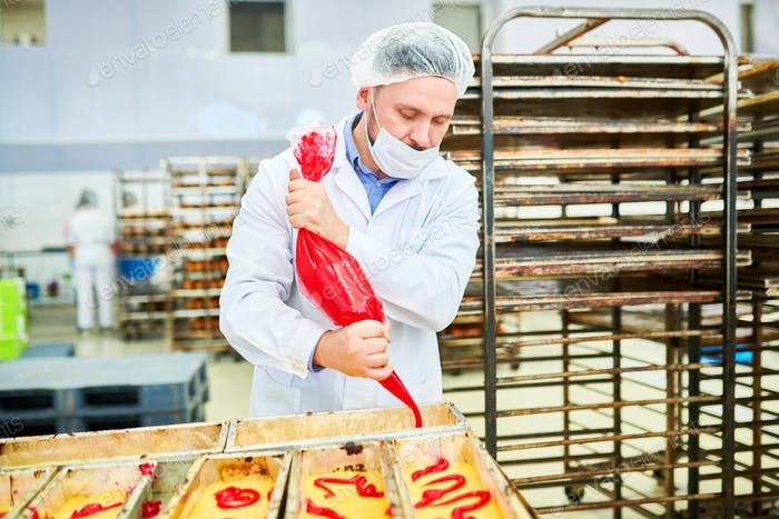 Confectionery factory employee using icing bag