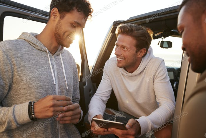 Three male friends on a road trip using a tablet, close up