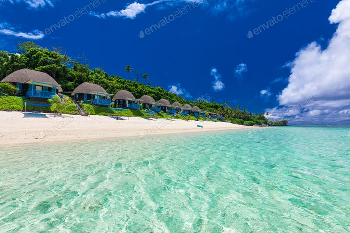 Tropical beach with with palm trees and villas, Polynesia