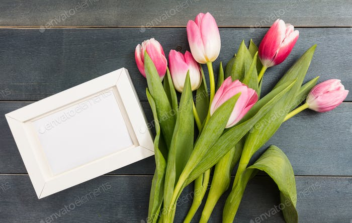Mother's day. Pink tulips and a white blank frame on blue background, copy space, top view