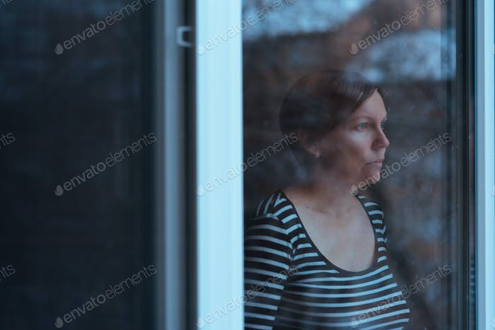Depressed woman standing by the window and looking outside
