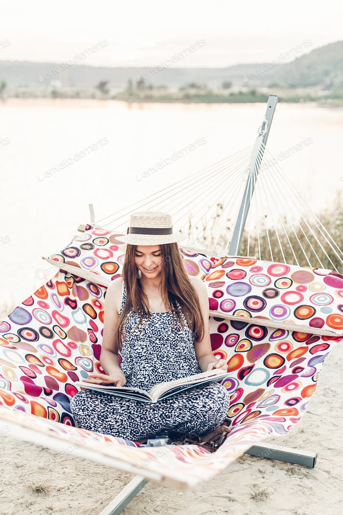 Beautiful hipster woman relaxing in a hammock and reading book