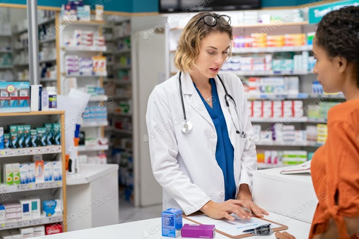 Pharmacist giving medicine with prescription to customer