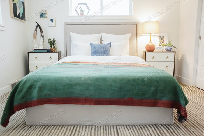 A green fabric quilt with red trim over a double bed in a light airy apartment.