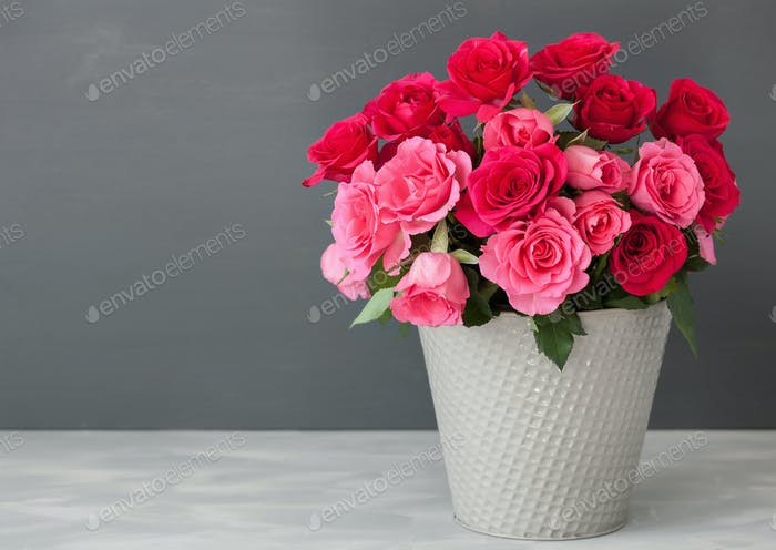 beautiful red rose flowers bouquet in vase over gray