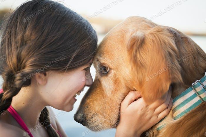 A young girl and a golden retriever dog, nose to nose.