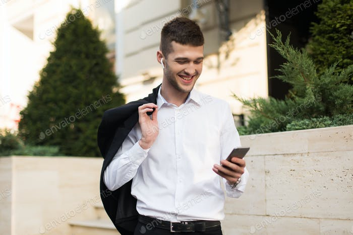 Young cheerful man in white shirt with wireless earphones holdin