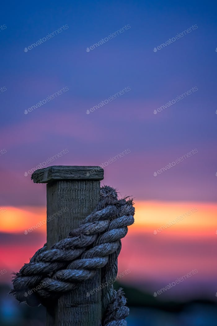 Thick rope tied around a wooden fence