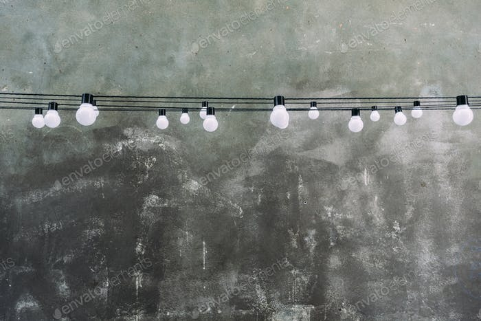 Light bulbs hanging on cables against gray industrial wall