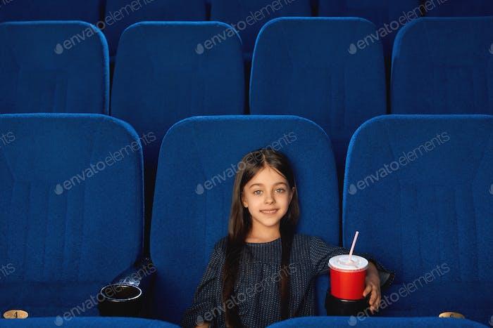 Little smiling girl sitting in empty cinema