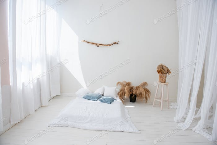 Minimalistic white loft in Scandinavian interior style. There is bed on wooden floor
