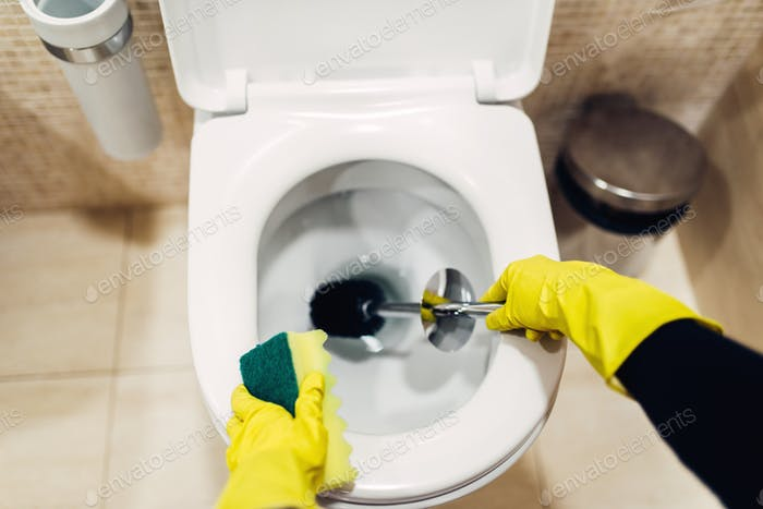 Housemaid in gloves cleans the toilet with brush