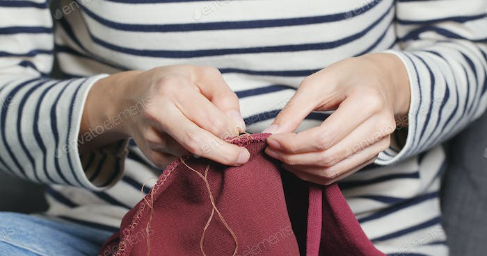 Woman Sews with a needle and thread