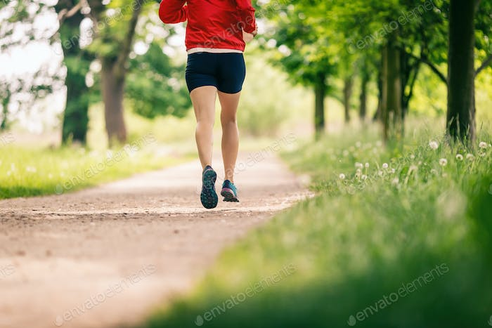 Running woman, enjoying summer day in park