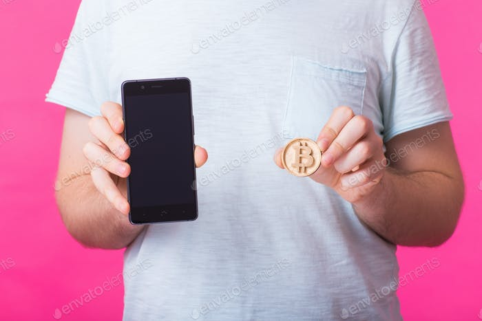 Man showing wooden bitcoin and blank screen mobile phone.