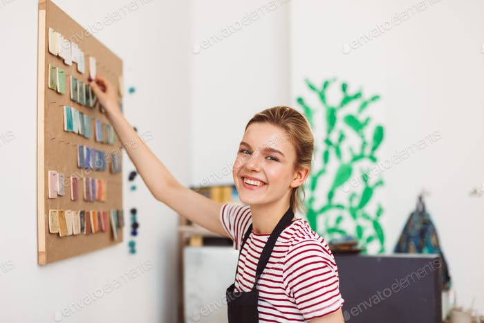 Pretty smiling girl in black apron standing near colorful materials board happily looking in camera