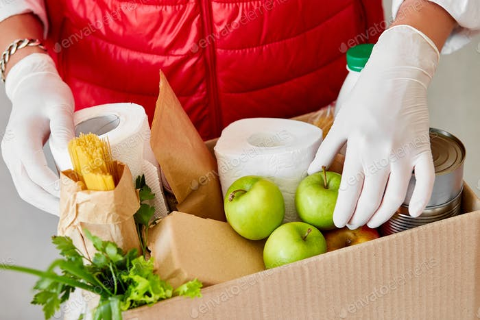 Volunteer in the protective medical mask and gloves putting food In donation box.