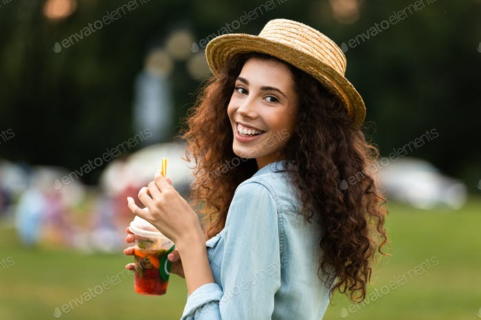 Image of brunette woman 20s wearing straw hat, smiling and drink