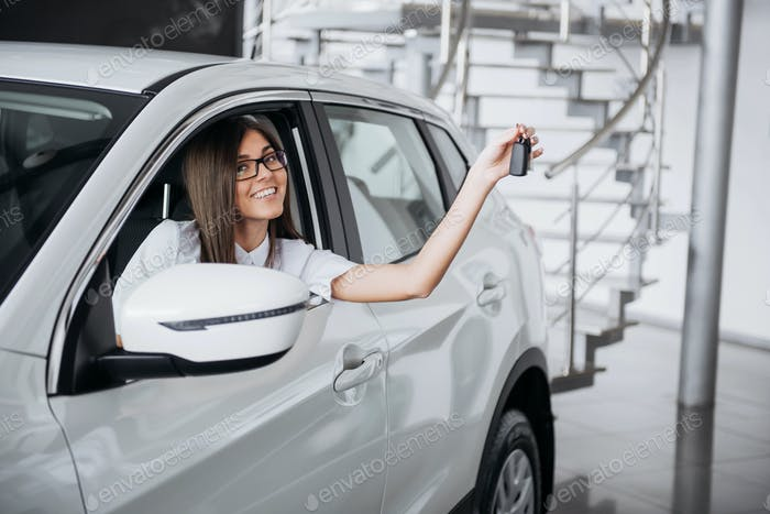 Junge glückliche Frau in der Nähe des Autos mit Schlüsseln in der Hand